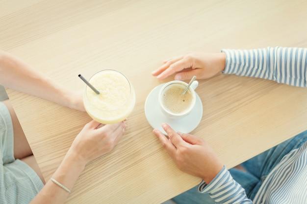 Vrouwelijke paar het drinken koffie en smoothie bij koffie. plat leggen. bovenaanzicht