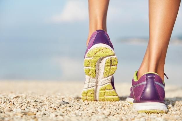 Vrouwelijke paarse sneakers staat op shell strand, draagt sportschoenen. sport en een gezonde levensstijl concept