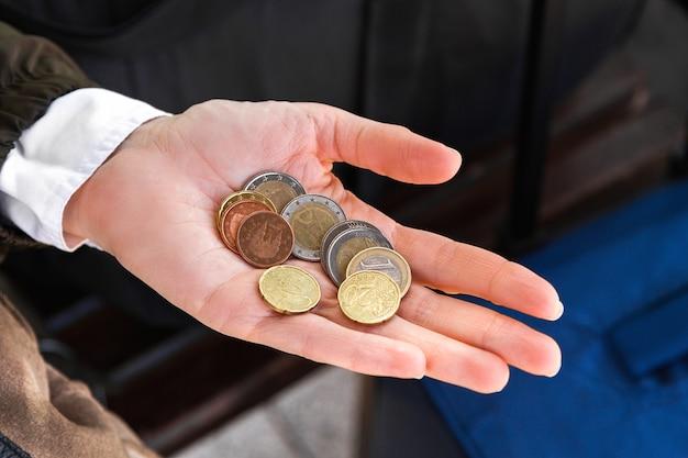 Vrouwelijke palm met een handvol munten van euro.