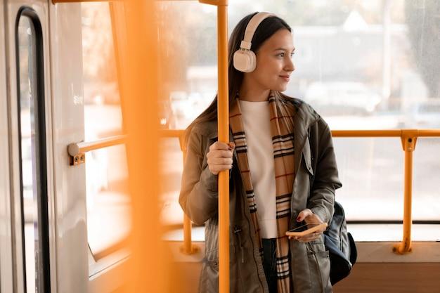 Vrouwelijke passagier die de trampaal houdt
