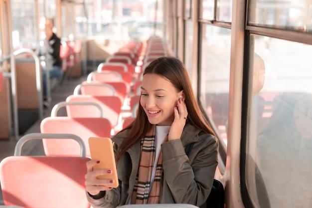 Vrouwelijke passagier die haar mobiele telefoon gebruikt in het openbaar vervoer