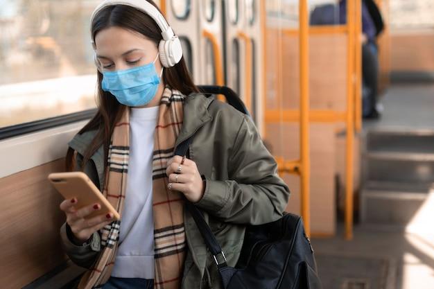 Vrouwelijke passagier die medisch masker draagt en aan muziek luistert