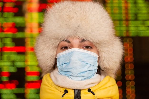 Vrouwelijke passagier op het station, een bord met vertrekroutes op de achtergrond, een beschermend masker op haar gezicht