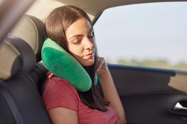 Vrouwelijke passagier slaapt in de auto tijdens het rijden op lange afstand