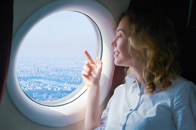 Vrouwelijke passagier van het vliegtuig kijkt met belangstelling naar de stad beneden buiten het raam