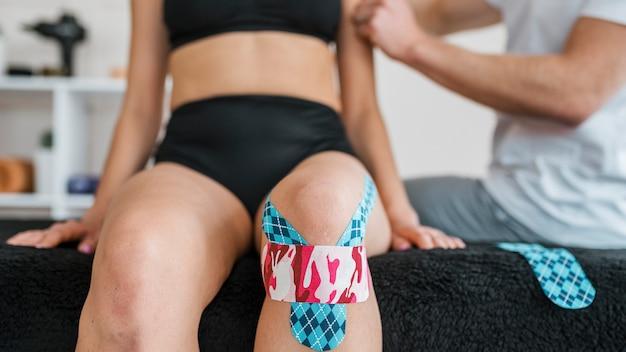 Vrouwelijke patiënt bij fysiotherapie met kniebrace tape