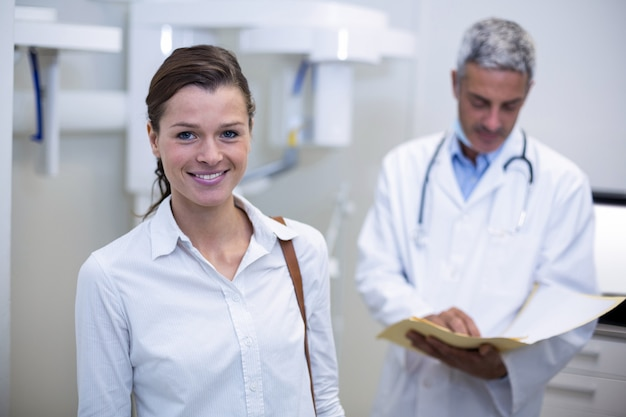 Vrouwelijke patiënt die bij tandkliniek glimlacht