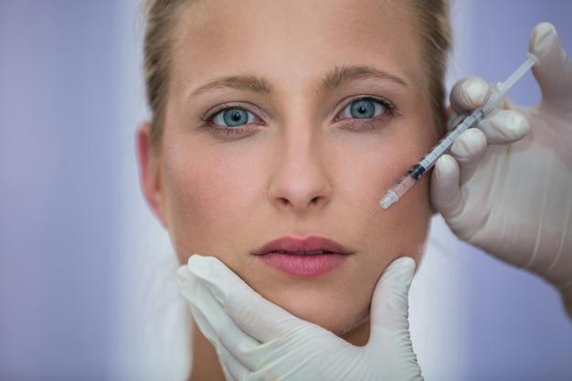Vrouwelijke patiënt die een botoxinjectie op gezicht ontvangt