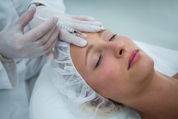 Vrouwelijke patiënt die een botoxinjectie op voorhoofd ontvangt