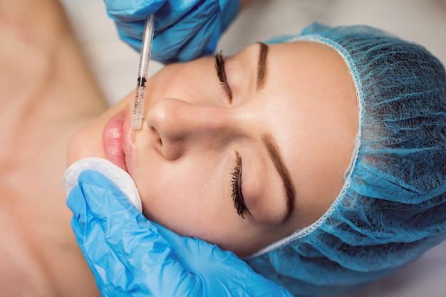 Vrouwelijke patiënt die een injectie op haar gezicht ontvangt