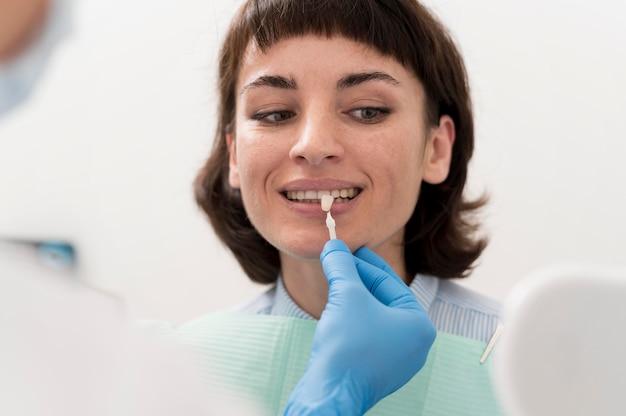 Vrouwelijke patiënt die in de spiegel kijkt op het kantoor van de tandarts