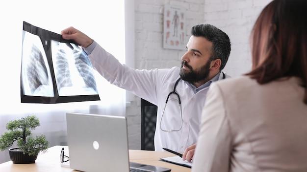 Vrouwelijke patiënt die mannelijke huisarts in medisch bureau bezoekt die diagnoseresultaat op röntgenstraalfilm krijgt