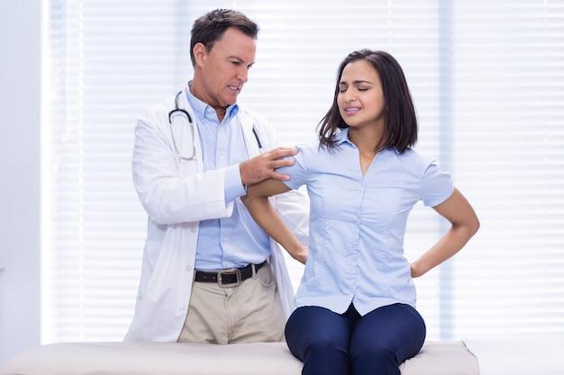 Vrouwelijke patiënt die rugpijn toont aan arts