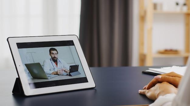Vrouwelijke patiënt in een videoconferentie vanuit huis met haar arts.