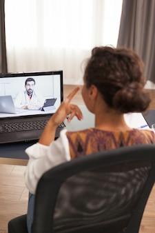 Vrouwelijke patiënt in een videogesprek met arts die over haar medicijn praat.