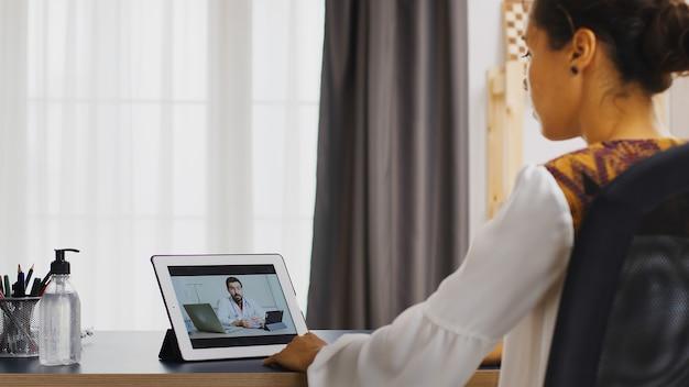 Vrouwelijke patiënt in een videogesprek met haar arts die over haar ziekte praat.