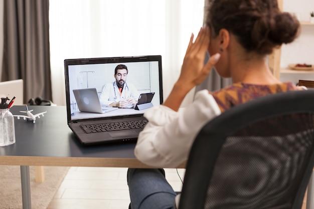 Vrouwelijke patiënt in een videogesprek met haar arts vanuit huis.