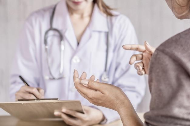 Vrouwelijke patiënt in gesprek met de dokter in een hospita