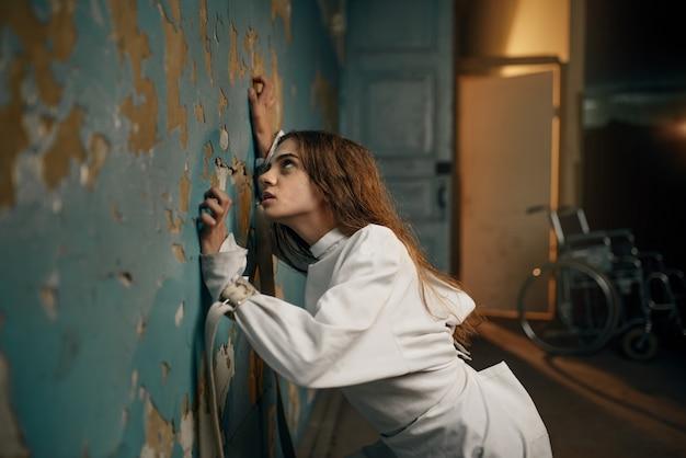 Vrouwelijke patiënt in keurslijf, psychiatrisch ziekenhuis.