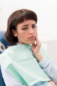 Vrouwelijke patiënt met kiespijn op het kantoor van de tandarts dentist