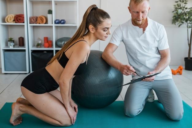 Vrouwelijke patiënt met mannelijke fysiotherapeut die klembord bekijkt
