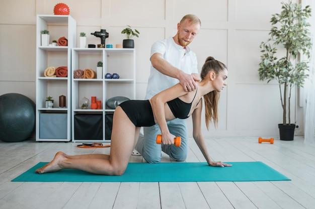 Vrouwelijke patiënt met mannelijke fysiotherapeut en halter