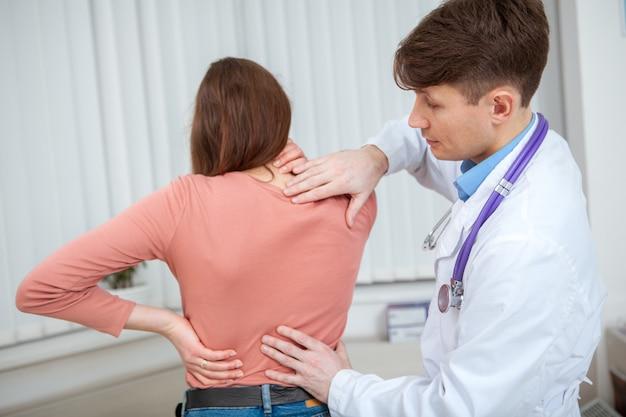 Vrouwelijke patiënt met rugpijn die door arts wordt onderzocht