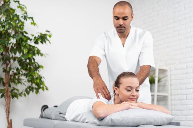 Vrouwelijke patiënt wordt gecontroleerd door mannelijke fysiotherapeut