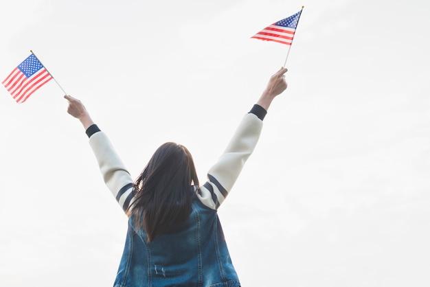 Vrouwelijke patriot met vlaggen in uitgestrekte handen