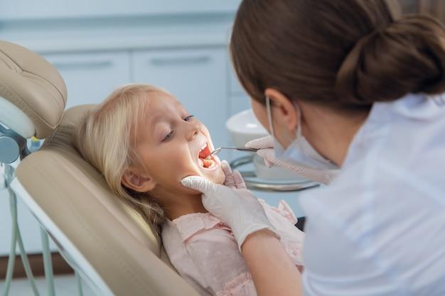 Vrouwelijke pediatrische tandarts en haar kleine patiënt