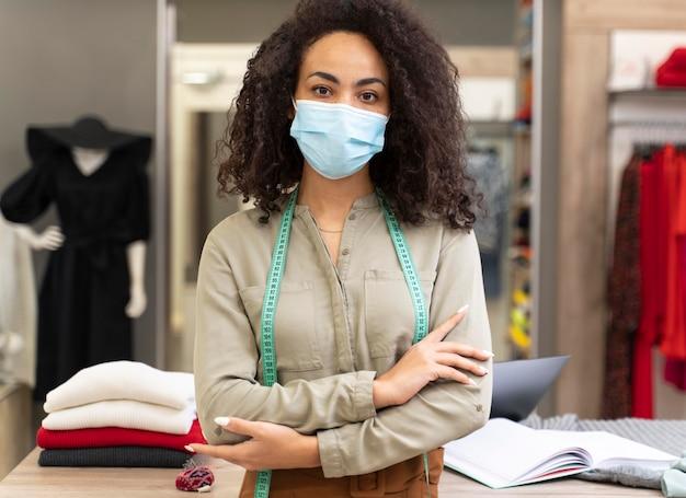 Vrouwelijke personal shopper met masker werken