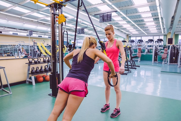 Vrouwelijke personal trainer die aan vrouw lesgeeft in een training met harde ophanging met fitnessriemen op een fitnesscentrum