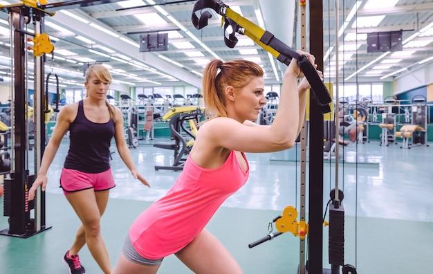 Vrouwelijke personal trainer helpt vrouw in een suspension-training met fitnessriemen op een fitnesscentrum fitness