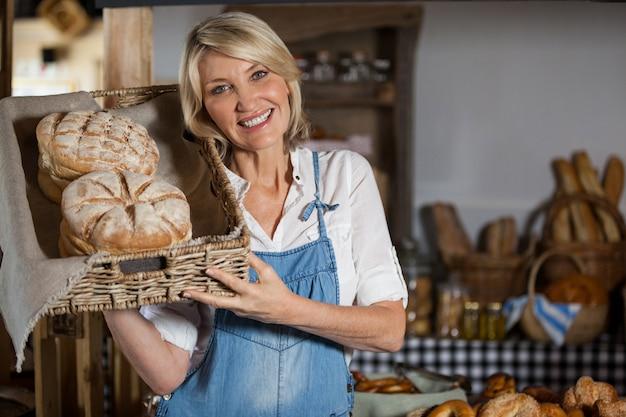Vrouwelijke personeel mand met zoete voedingsmiddelen in bakkerij sectie te houden