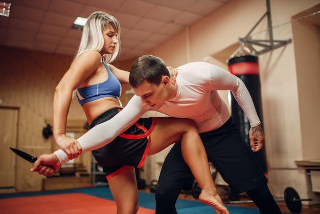 Vrouwelijke persoon beoefenen van een knie-kick naar de maag op zelfverdedigingstraining met mannelijke personal trainer, sportschool interieur. vrouw op training, zelfverdedigingsoefening
