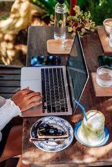 Vrouwelijke persoon die een moderne laptop gebruikt in het park buiten aan tafel zitten, er is telefoon en eten met wat drankjes.