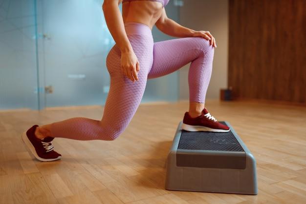 Vrouwelijke persoon die oefening met tribune in gymnastiek doet, yogatraining.