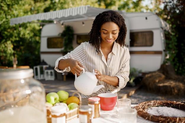 Vrouwelijke persoon die ontbijt kookt in de buurt van de camper, kampeerwagen. stel reist op busje, vakanties op camper