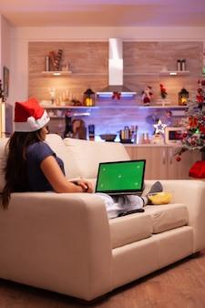 Vrouwelijke persoon die op de bank rust in een met kerst versierde keuken met groen scherm mock up chroma key lapto