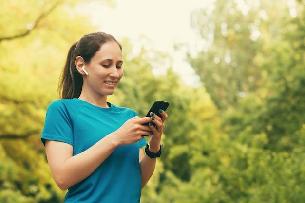 Vrouwelijke persoon gebruikt haar telefoon, draag draadloze oortelefoons in het bos tijdens het hardlopen.