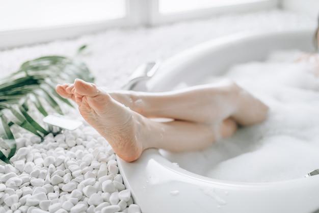 Vrouwelijke persoon hielen steken uit het bad met schuim. ontspanning, gezondheid en lichaamsverzorging in de badkamer