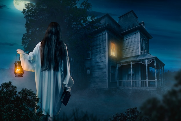 Vrouwelijke persoon in wit overhemd houdt kerosinelamp en spreukenboek in de hand tegen verlaten huis, maanverlichte nacht, achteraanzicht.