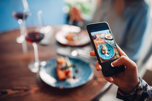 Vrouwelijke persoon maakt shot van rode wijn en zoet dessert op tafel in restaurant. chocoladetaart en alcohol