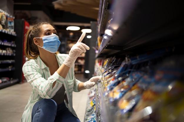 Vrouwelijke persoon met masker en handschoenen die voedsel in supermarkt kopen