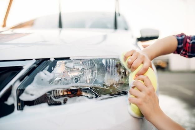 Vrouwelijke persoon met spons reinigt voertuig koplamp, autowassen. jonge vrouw bij het wassen van de zelfbediening auto. buiten carwash op zomerdag