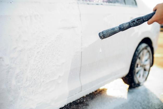 Vrouwelijke persoon met waterpistool wast het schuim af