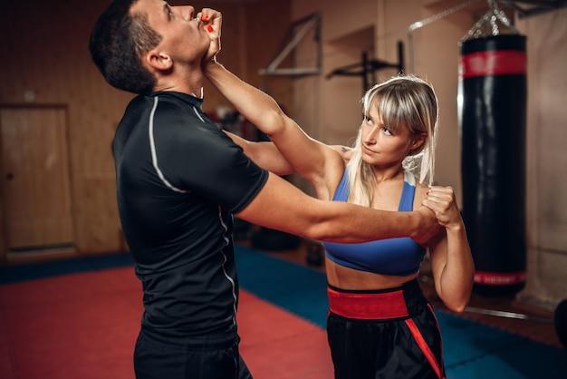 Vrouwelijke persoon op zelfverdedigingstraining met mannelijke persoonlijke trainer