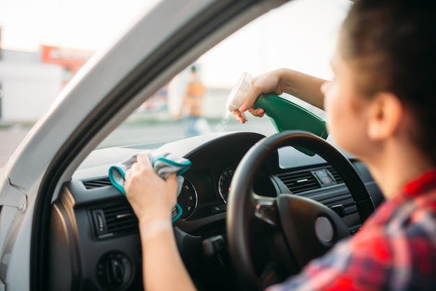 Vrouwelijke persoon poetst het dashboard van de auto