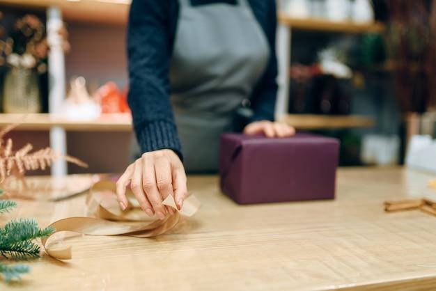 Vrouwelijke persoon versiert geschenkdoos met gouden lint, inpakpapier, decoratieproces. vrouw wraps aanwezig op tafel, decorprocedure