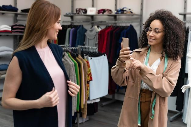Vrouwelijke persoonlijke shopper die foto's van cutomer neemt